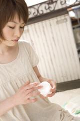 クリームを指に取る女性