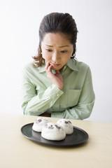 和菓子を眺めて悩む中年女性