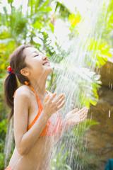 シャワーを浴びる水着の女性