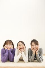 フローリングの上に寝そべる女性3人