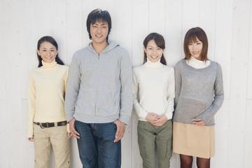 白い壁の前に立つ男女4人