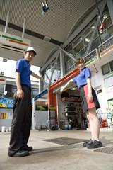 ガソリンスタンドに手招きする男女店員