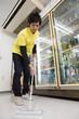 店内の床を清掃する男性店員