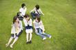 芝生に座る男女5人