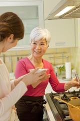 料理の味見をする女性2人