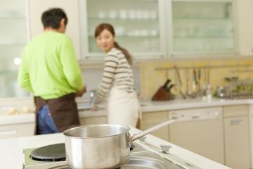 コンロの上の鍋と男女