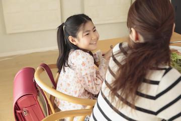 食卓で母親に話しかける娘