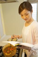 本を眺めながら料理をする女性