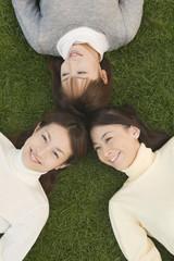 芝生の上に寝そべる女性3人