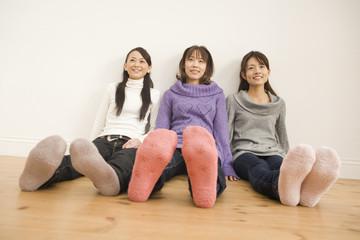 フローリングの上で足を投げ出す女性3人