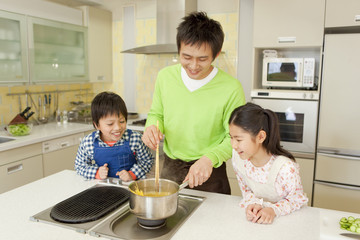 スパゲティを茹でる父親と子供2人
