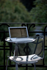 weißer Laptop auf rundem Glastisch und Plexiglasstuhl auf Balkon