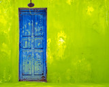 Blue Door in Shabby Green Wall poster