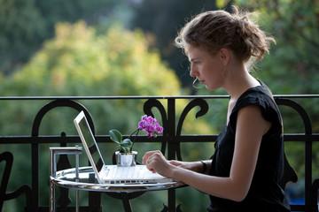 jung Frau schreibt auf einem weißen Laptop auf dem Balkon