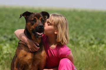 jeune fille embrassant tendrement son chien dans le cou