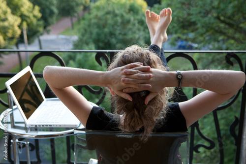 Leinwanddruck Bild junge blonde Frau entspannt, Füße hoch, vor Laptop auf Balkon