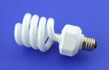 A compact fluorescent light bulb against a blue background.