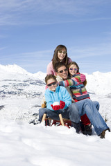 Family sledding on ski slope