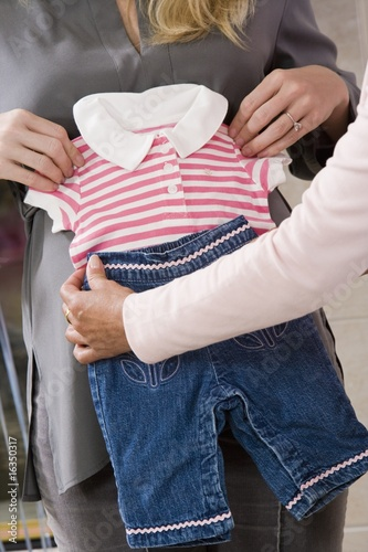 Pregnant Woman with Baby Clothes at a Baby Shower