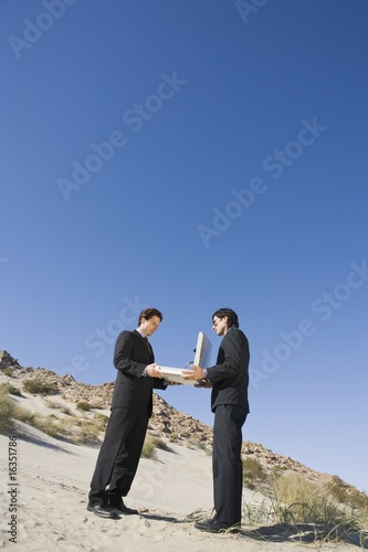 Two Businessmen Holding Open Briefcase in the Desert
