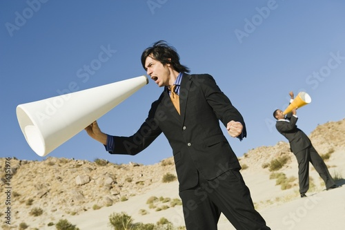 Two Businessmen Using Megaphones in Desert