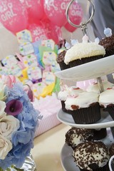 Baby Shower Gifts and Cupcakes arranged on Table