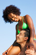 Summer couple - bikini girl sitting on shoulders of man