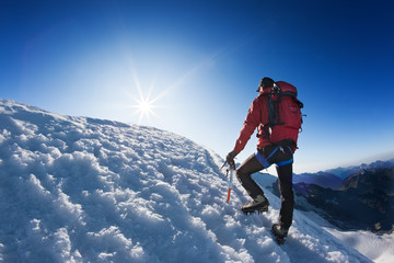 Mountaineer reaches the top of a high mountain peak.