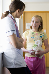 Nurse talking to girl holding stuffed animal