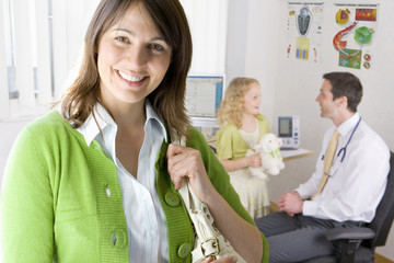 Woman in office smiling with doctor and girl in background