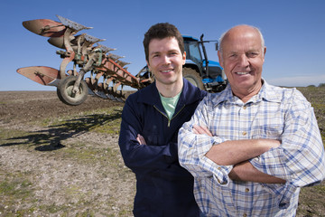 Farmers standing with arms crossed in field with tractor and plough in background