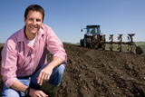 Smiling farmer crouching in ploughed field with tractor and plough in background