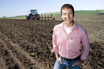 Smiling farmer standing in ploughed field with tractor and plough in background