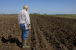 Farmer holding laptop in ploughed field