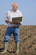 Farmer using laptop in ploughed field
