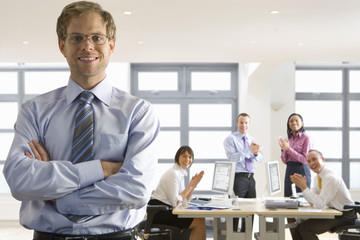 Business people in office applauding smiling businessman with arms crossed
