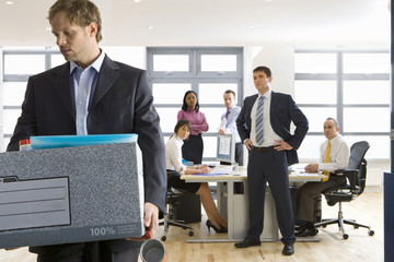 Business people watching businessman leave office with box of belongings