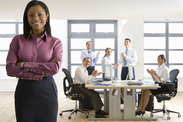 Business people in office applauding confident businesswoman