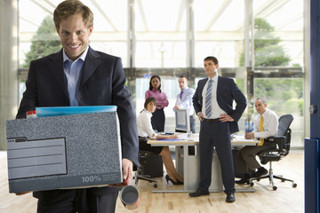 Business people watching smiling businessman leave office with box of belongings