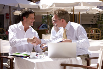 Businessmen surrounded by paperwork and laptop shaking hands at sunny, outdoor cafe