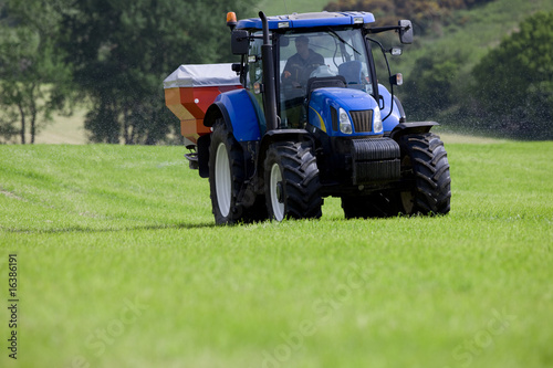 Tractor spreading fertilizer in field