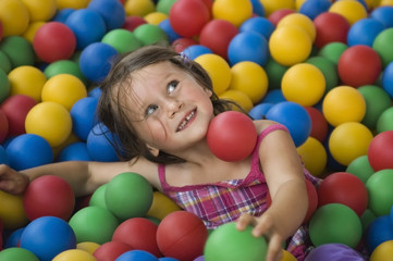 Little girl having fun time in balls pool