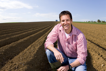 Smiling farmer crouching in ploughed field