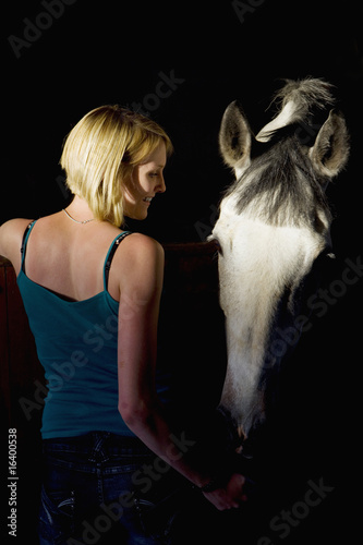 Woman feeding horse in stable