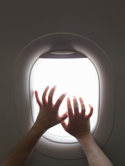 Hands clawing at airplane window