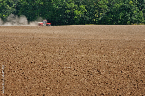 tractor cultivating on field