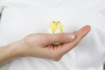A woman holding an Easter chick toy, close-up