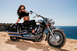 The beautiful girl on a motorcycle on a background of the sea