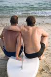 two gay men sitting on surfboard cuddling at the beach. poster