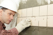 Man installs ceramic tile on a wall
